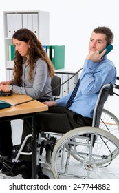 man in wheelchair and his  is female colleague working in the office