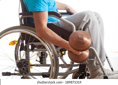 Man in wheelchair lifting weight on isolated white background