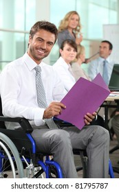 Man in wheelchair looking at notes