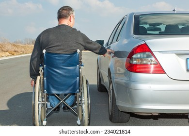 Man in a wheelchair next to his car