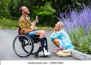 Mann im Rollstuhl im Freien, der Gitarre für eine blonde Frau spielt, die an einem Bordstein sitzt