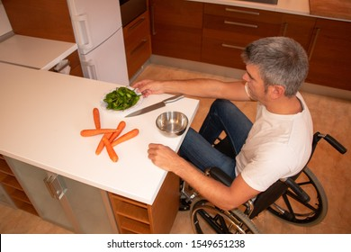A man in a wheelchair preparing food in the kitchen. Disability concept