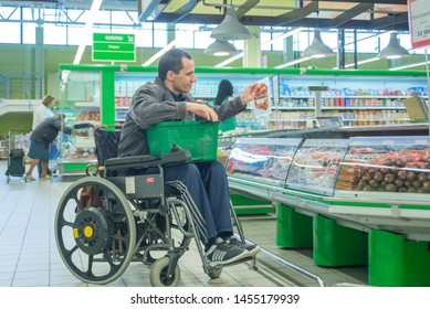 Man in wheelchair shopping in a store. June 20, 2019, Belarus, Grodno