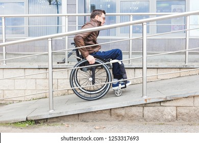 Man in a wheelchair use a wheelchair ramp.