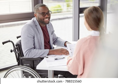 Man in wheelchair work in his own company as director, gives commands and instruction to female secretary, happy to receive high profit