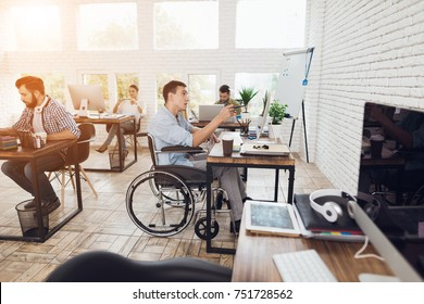 A man in a wheelchair is working in a bright office. His colleagues are passionate about work. The man looks thoughtfully at the screen.