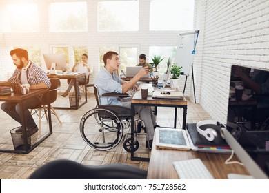 Un homme en fauteuil roulant travaille dans un bureau lumineux. Ses collègues sont passionnés par le travail. L'homme regarde attentivement l'écran.