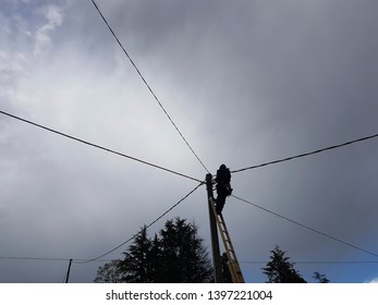 man while working on an electricity pole