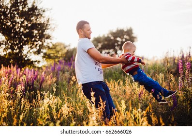 Man whirls little son on the field covered with evening lights