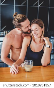 Man whispering in girlfriend's ear while she is smiling in the kitchen
