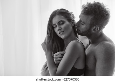 Man whispering to his woman in erotic way