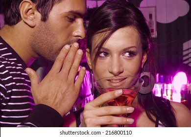 Man whispering into a young woman's ear in a bar
