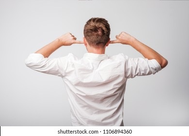 Man in whit shirt with closed ears turning back to the camera. He does not want to hear information.