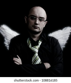 Man with white angel wings behind. Over black background. In studio.