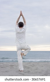 Man in white cloths doing yoga on a beach