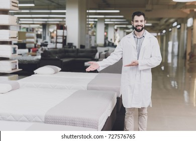 A man in a white coat poses as an orthopedist. He is standing in a large mattress and bed-clothes store and points to one of the mattresses
