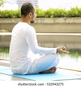Man is white is doing meditation by the poolside in the morning.