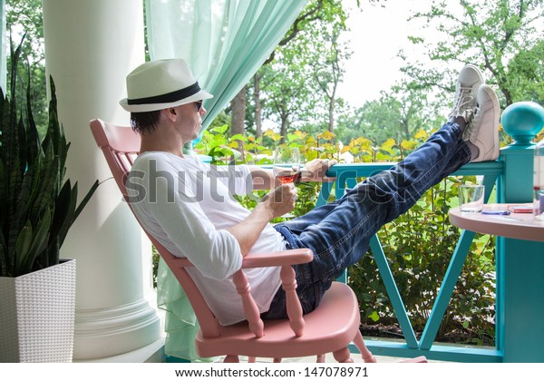 Man in a white hat and with glass of wine resting on the summer terrace