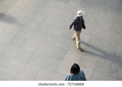 Man in a white hat and jacket and an Asian woman walk through a train station in Europe.  Looking down on two people from above.