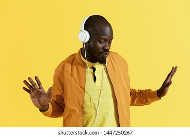 Man in white headphones listening music, dancing closeup portrait on yellow background. Handsome black male model in earphones and stylish clothes enjoying sound in studio