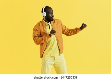 Man in white headphones listening music, dancing portrait on yellow background. Handsome black male model in earphones and stylish clothes enjoying sound in studio