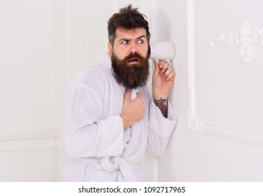 Man in white interior spying, eavesdropping. Secret and spy concept. Man with beard and mustache eavesdrops using mug near wall. Hipster in bathrobe on strict face secretly listen conversation