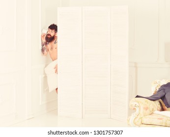 Man in white interior spying, eavesdropping. Man with beard and mustache eavesdrops using mug near wall. Hipster naked on shocked face secretly listen conversation. Lovers and cheating concept.