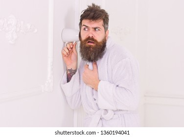 Man in white interior spying, eavesdropping. Secret and spy concept. Man with beard and mustache eavesdrops using mug near wall. Hipster in bathrobe on strict face secretly listen conversation.
