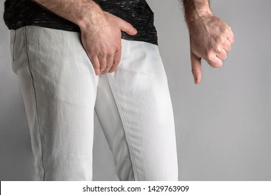 A man in white jeans holds his genitals and points with his thumb down. Disease for men. The concept of protection against sexually transmitted infections. Testicular cancer.
