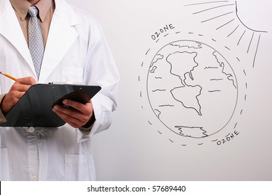 Man in a white lab coat writing down information about the ozone layer.