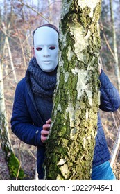 man with white mask hiding behind a tree