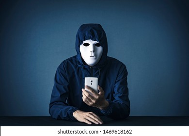 A man with a white mask holding a smartphone