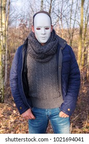 man with white mask standing outdoors in the woods