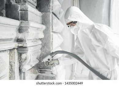 A man in a white protective uniform cleans stone carved sculpture from the dirt and concrete with a sandblasting machine. Restoration of stone sculpture. A jet of sand under high pressure.