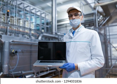man in a white robe and a mask with a laptop in his hands is at the factory