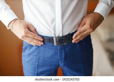 A man in a white shirt and blue trousers without a face holds his hands on a brown leather belt. Groom's morning at the wedding.