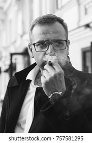 Man in a white shirt and coat is Smoking