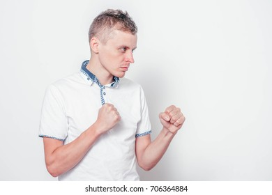 Man in white shirt doing fighting stance on white background