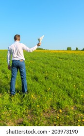 man in white shirt in the field with papers