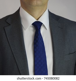 Man in white shirt, gray jacket and blue tie.