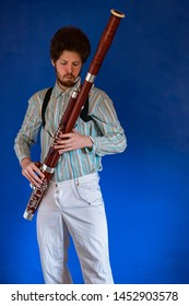 man with a white shirt and his bassoon standing in front of a blue wall