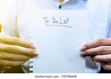 man in white shirt hold paper to do list