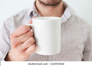 Man with white shirt is holding white coffee mug in his right hand