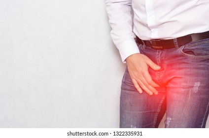 A man in a white shirt holding his groin with an infection and prostatitis, urology, copy space, inflammation