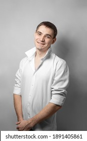 A man in a white shirt, holding his hands together and posing on a white background. Men's emotions, joy and fun