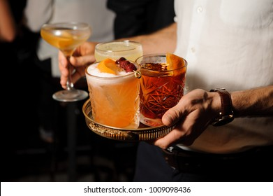 man in a white shirt is holding a tray with three glasses with amber Negroni and yellow sour mix, decorated with oranges and cherries