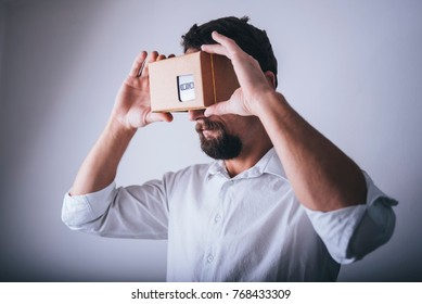 Man in white shirt holds cardboard glasses for virtual reality