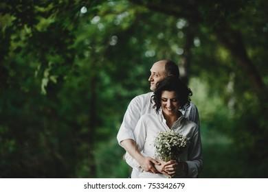 Man in white shirt hugs woman tender standing under green trees