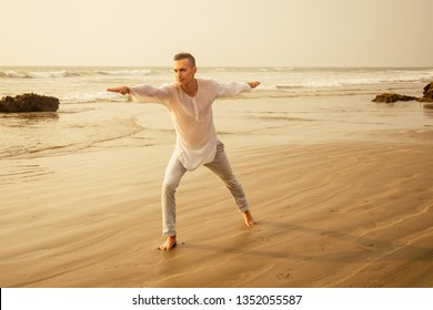 man in white shirt and pants acts yoga warrior pose on the beach in the morning silhouetted against sunlight.businessman balance