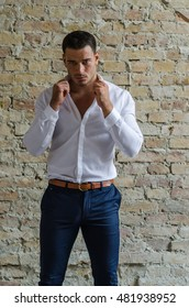 Man in a white shirt and pants posing in front of a brick wall